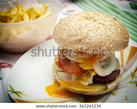 One delicious hamburger with French fries in the background.