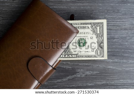 One dollar banknote in long brown wallet on black wooden table - stock photo