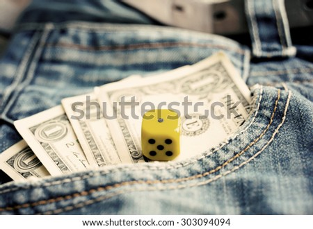 One dollar banknotes in pocket denim and a dice vintage toned