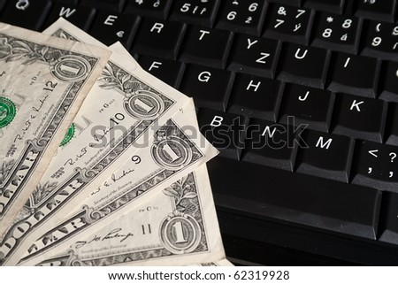 One dollar banknotes on laptop keyboard.