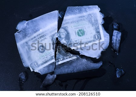 One dollar bill frozen and broken in ice and money rended. - stock photo