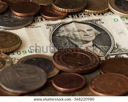 One dollar bill with various coins around - stock photo