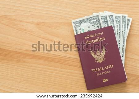 one dollar bills thai passport - stock photo