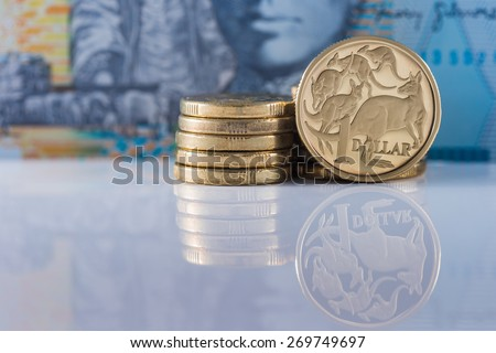 One Dollar Coin with Ten Dollar note in the background - Australian Currency