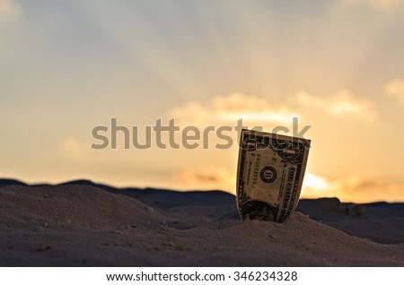 One dollar is on a sand - stock photo