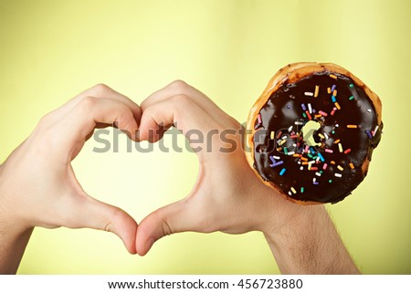 one donut and heart shape from hands isolated on yellow - stock photo