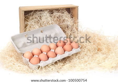 One dozen brown eggs in a carton on a bed of wood excelsior with a small crate in the background.