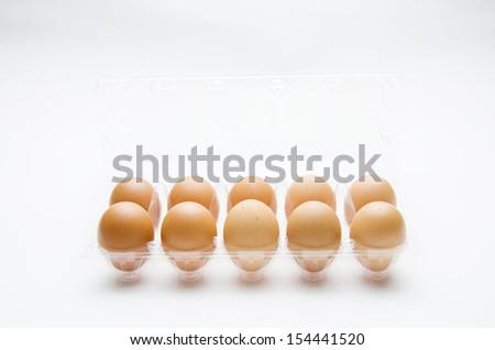 One dozen farm fresh eggs photographed on a white background.  - stock photo