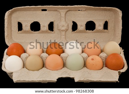 One dozen free range organic eggs of various sizes and colors in a recycled cardboard carton. - stock photo