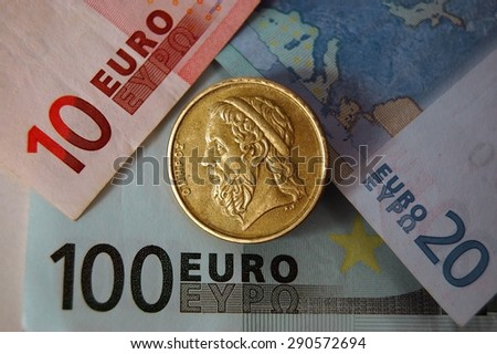 One drachma Greek coin on Euro notes.  - stock photo