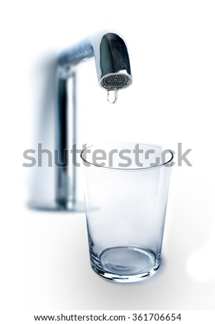 One drop of water dripping from the tap in an empty glass on white - stock photo