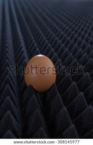 one egg on abstract bumpy black background with perspective view 1