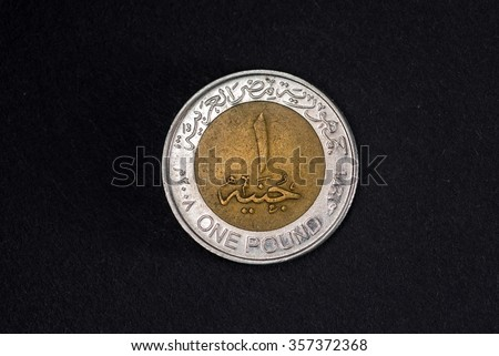 One Egyptian pound coin. Close up shot on black background. - stock photo