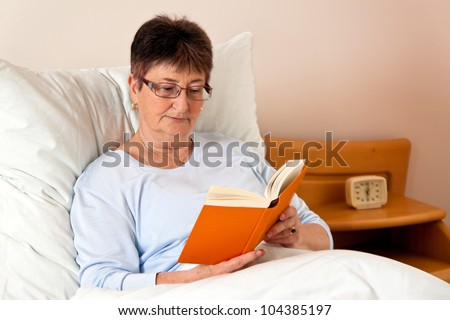 one elderly woman in a nursing home in bed reading the book