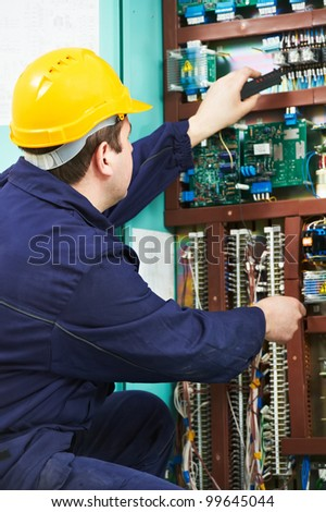 One electrician builder at work with multimeter checking current and voltage power at electric line distribution fuseboard - stock photo