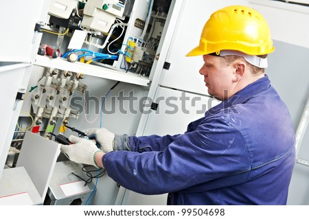 One electrician builder at work with tester measuring high voltage and current of power electric line in electical distribution fuseboard