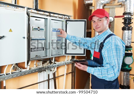 One electrician working with distribution fuseboard - stock photo