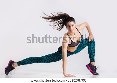 One energetic attractive gorgeous young fit modern dancer woman in aquamarine sportswear with ponytail working out, dancing, full length, studio image on gray background - stock photo