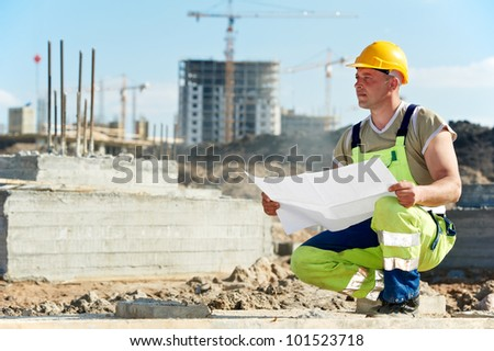 One engineer builder with blueprint plan draft at construction site - stock photo
