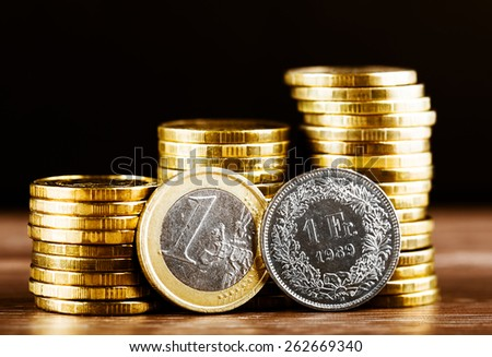 one euro coin and one swiss frank and gold money on the desk - stock photo
