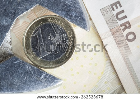 one Euro coin fixed in an adjustable wrench, financial concept for loss in value or currency devaluation of the Euro - stock photo