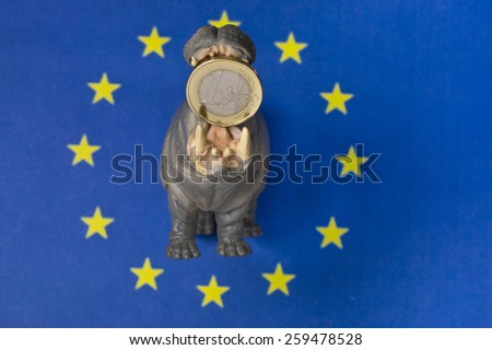 One euro coin in mouth of hippo figurine, Europe flag - stock photo