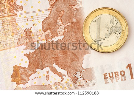 One Euro Coin on Euro Banknote showing Map of Europe - stock photo