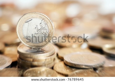 one euro coin on pile of euro coins in background - stock photo