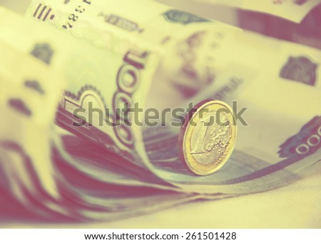 One euro coin on russian roubles banknotes. Finance concept. Vintage filter. - stock photo