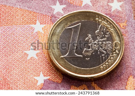 One Euro coin on ten Euros background - stock photo