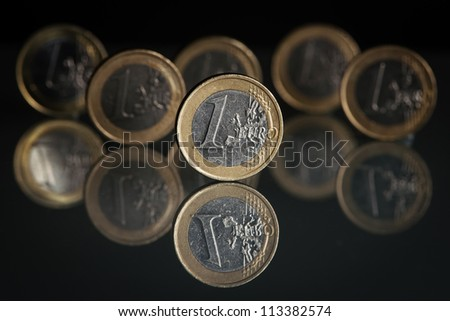 one euro coins on black background - stock photo