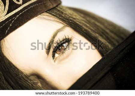 One eye close-up portrait of a Muslim girl. Aged photo. - stock photo