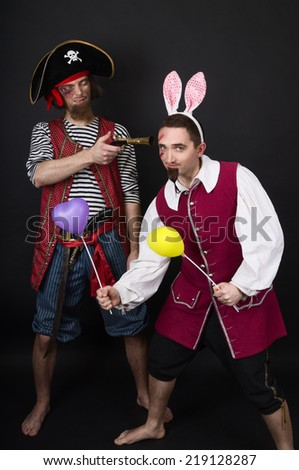 One-eyed pirate aiming the other pirate with heart-shaped balloons and overhead bunny ears
