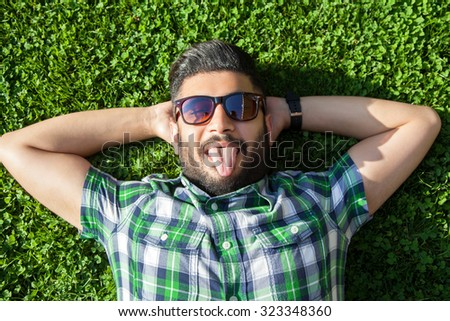 One fashion middle eastern man with beard, fashion hair style is resting on beautiful green grass day time. young arab businessman 20-30 years, resting after hard work. show tongue, funny and crazy - stock photo