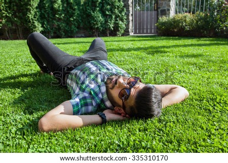 One fashion middle eastern man with beard, fashion hair style is resting on beautiful green grass day time. young arab businessman 20-30 years, resting after hard work. smart phone, tablet. - stock photo