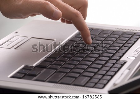 one finger typing on a laptop keyboard