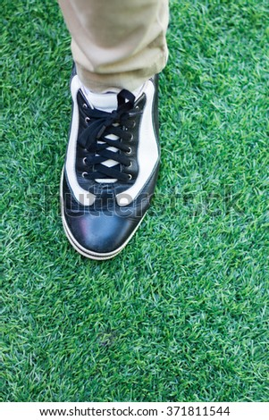 One foot with shoe step on artificial turf