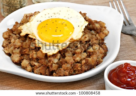 One fried egg, sunny side up, sits on top of roast beef hash.  Ketchup to the side.