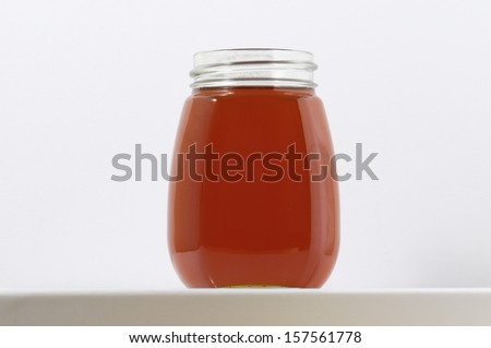 One Full Honey Jar on a White Background