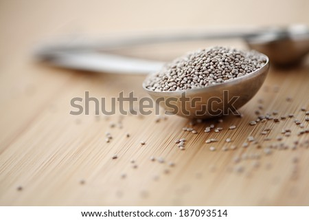 One full table spoon white chia seeds on a cutting board - stock photo