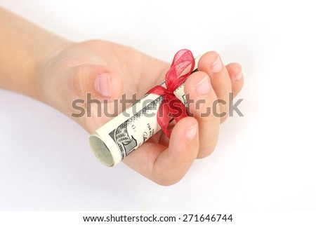 One gift of money american hundred dollar bills with red ribbon on a children's hand on white background - stock photo