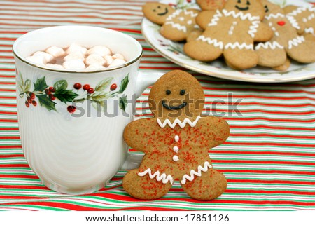 One gingerbread cookie standing by a full Christmas mug of hot chocolate with marshmallows.  Full plate of cookies in the background. - stock photo