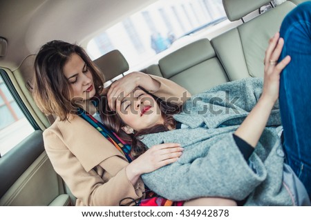 One girl helps another to cope with a headache. The ride in the car to the hospital.