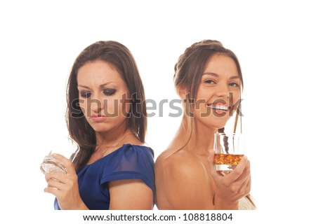 One girl is disappointed because of empty glass while other is happy to have it filled - stock photo