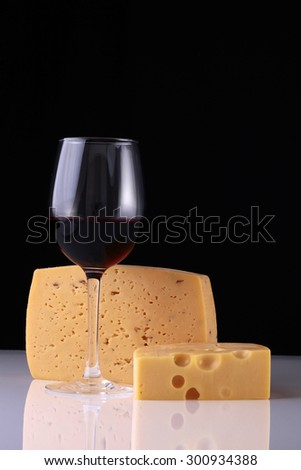 One glass bocal of red wine standing with two kinds of fresh tasty cheese reflecting on white table top on black studio background copyspace, vertical picture - stock photo