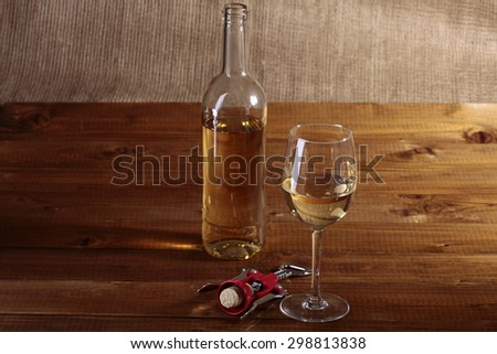 One glass bottle and goblet with white wine standing on brown wooden table top near red plastic and metal corkscrew on burlap background copyspace, horizontal picture - stock photo