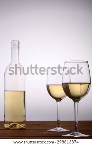 One glass bottle and two goblets of white wine standing on brown wooden table top isolated on grey white background copyspace, vertical picture - stock photo
