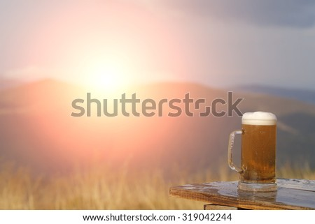One glass mug with lager or porter tasty frothy beer on wooden table top sunny day outdoor on natural with mountain hills and yellow dry grass background with flash light copyspace, horizontal picture - stock photo
