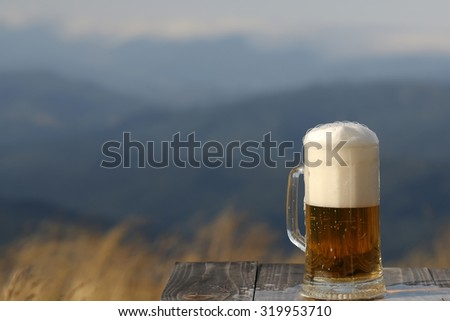 One glass mug with lager or porter tasty frothy beer on wooden table top sunny day outdoor on natural with mountain hills and yellow dry grass background copyspace, horizontal picture - stock photo