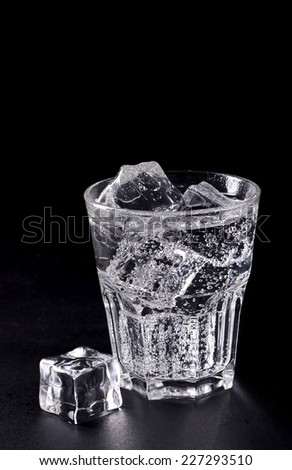 One glass of drink with ice on a black background